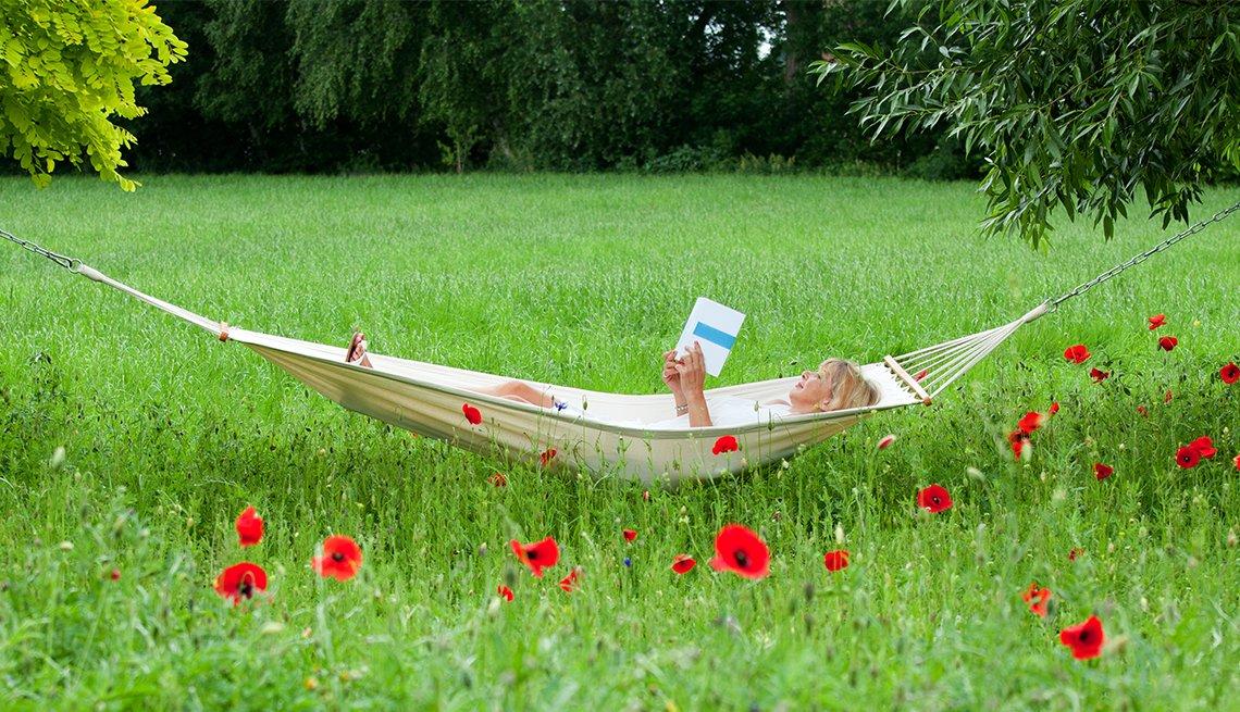 Mature woman lying on hammock in garden reading book.