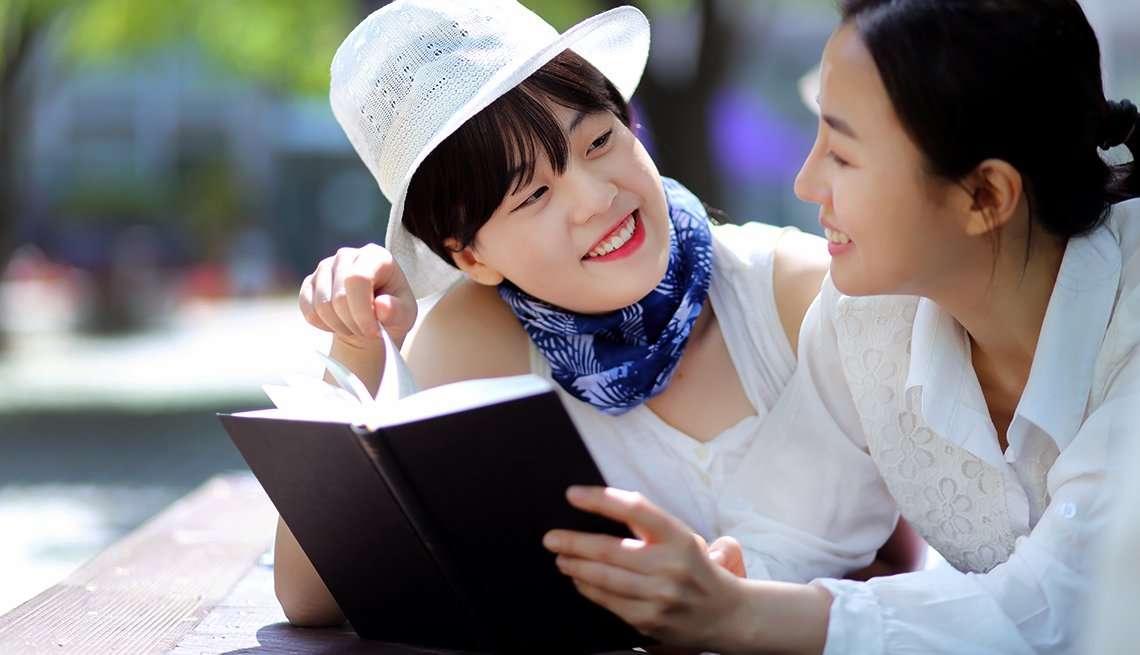 two mature asian women read together