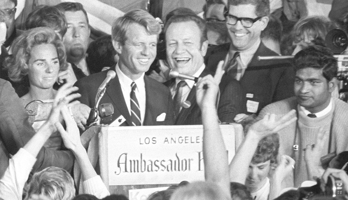 Robert F. Kennedy standing at a podium, sign in front reads Los Angeles Ambassador Hotel