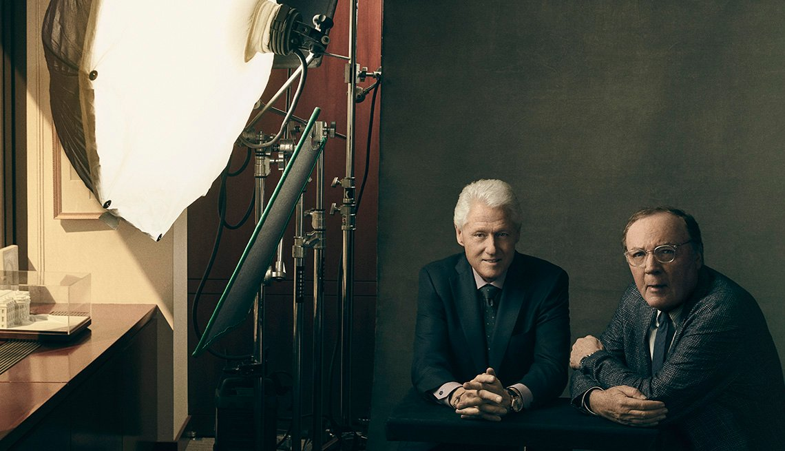 Bill Clinton and James Patterson sitting in front of a light