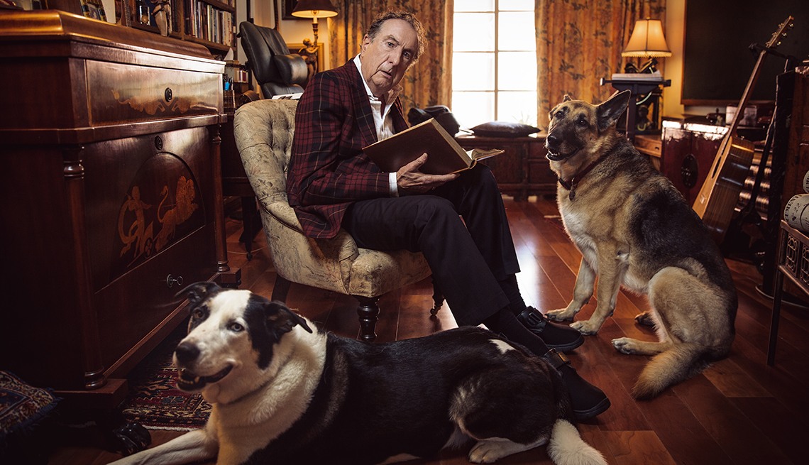 Eric Idle with his dogs holding a book