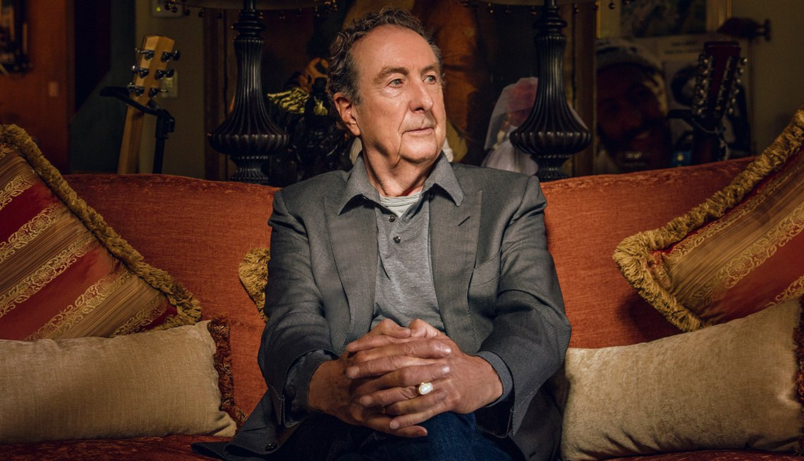 Eric Idle sitting on a couch