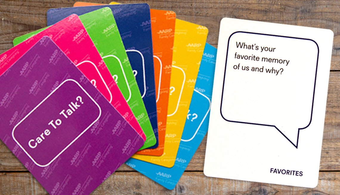 product photo of the family card deck on a wooden table. shown are a fan of seven different colored card backs that read care to talk, and a sample question card that asks, what is your favorite memory of us and why