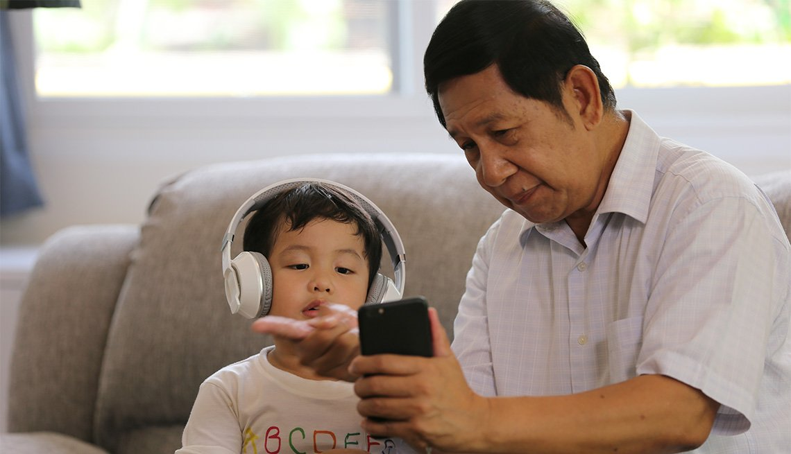 grandpa plays an audiobook on a cell phone for his grandson