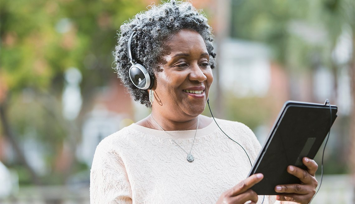 Close up of a senior, African American woman wearing headphones and using a digital tablet.  She could be listening to music or an audio book.