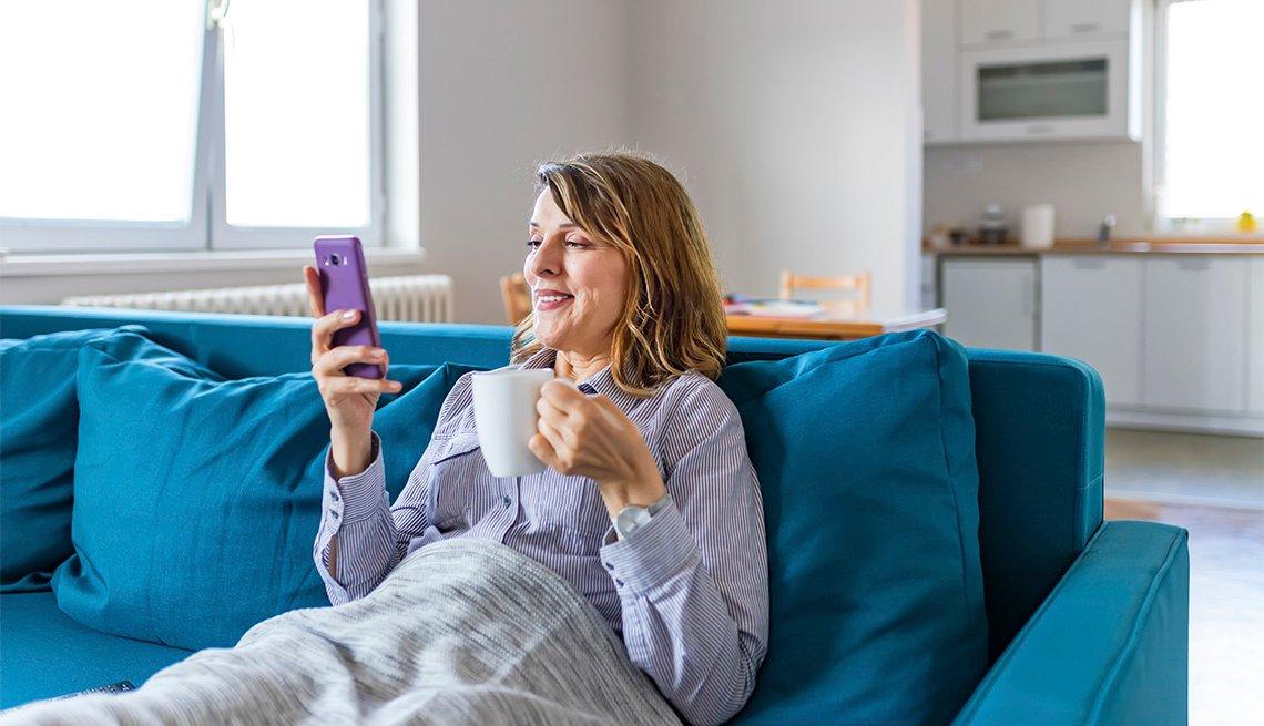 Mujer en un sofá con una tasa en una mano y un teléfono móvil en la otra.