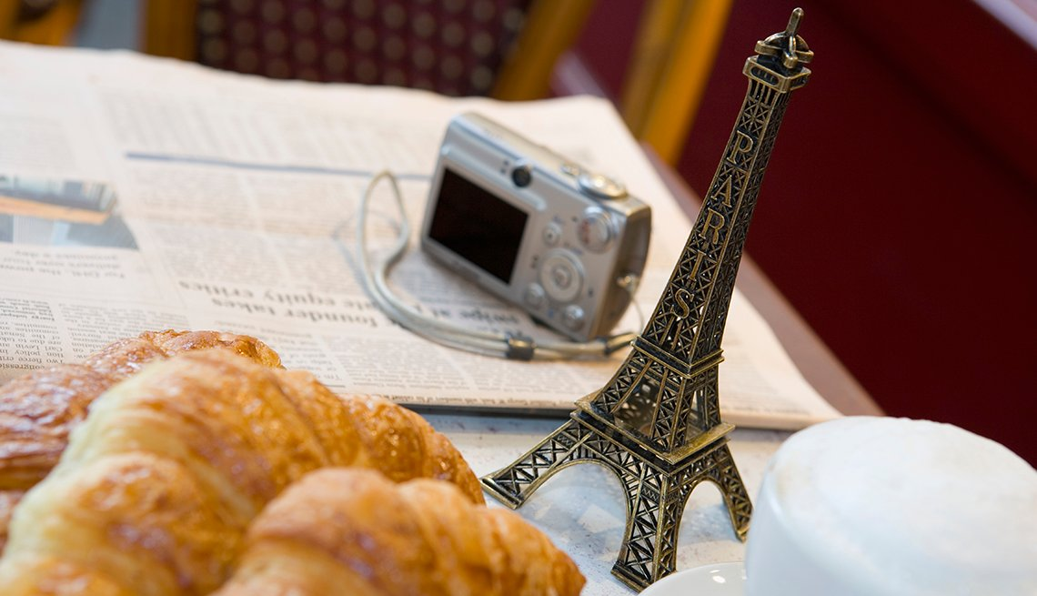overhead shot of a cafe table filled with a newspaper, camera, small metal eiffel tower souvenir foamy coffee drink and croissants