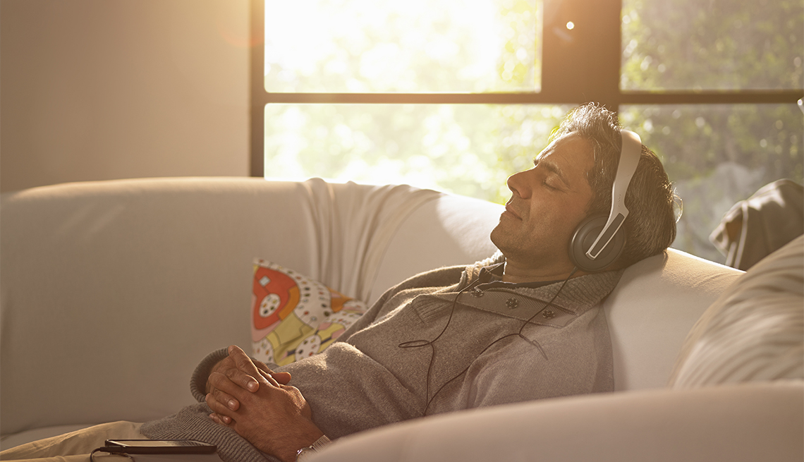 A man relaxing at home listening to music or a podcast