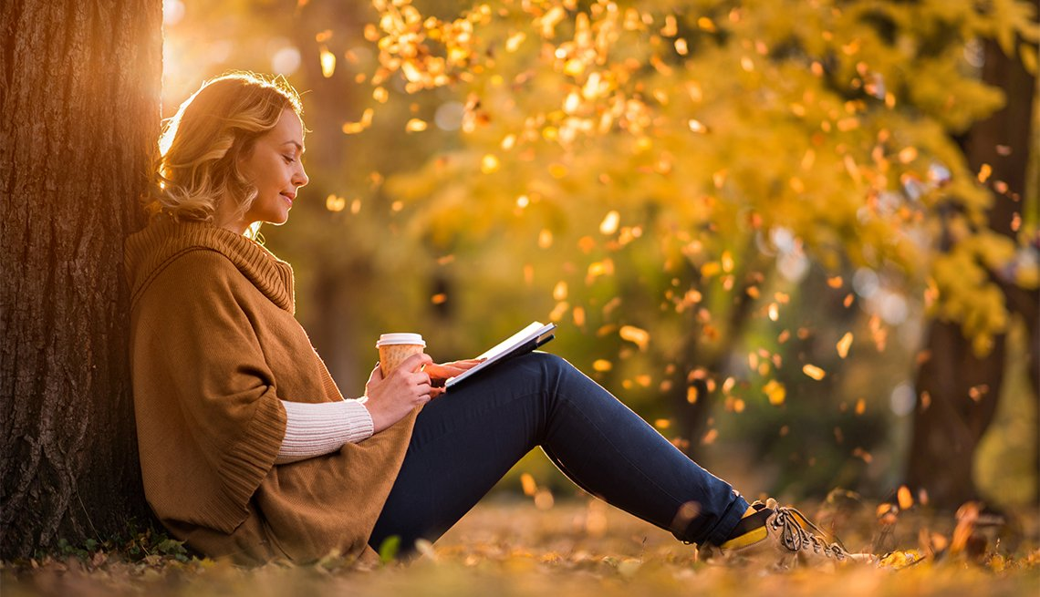 Woman sitting in the park and reading a novel
