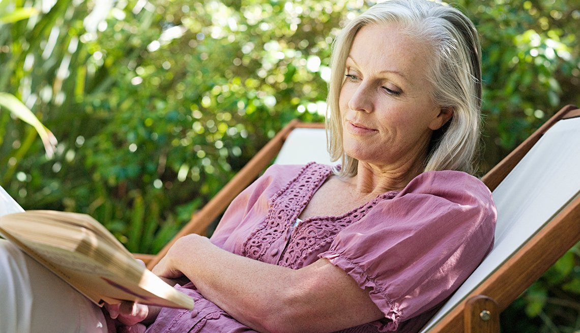 woman sitting on deck chair in garden reading a book