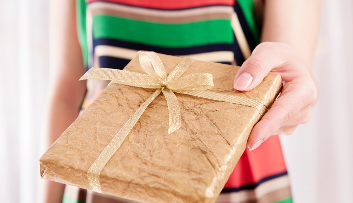close shot of a woman holding out a gift wrapped book as a present