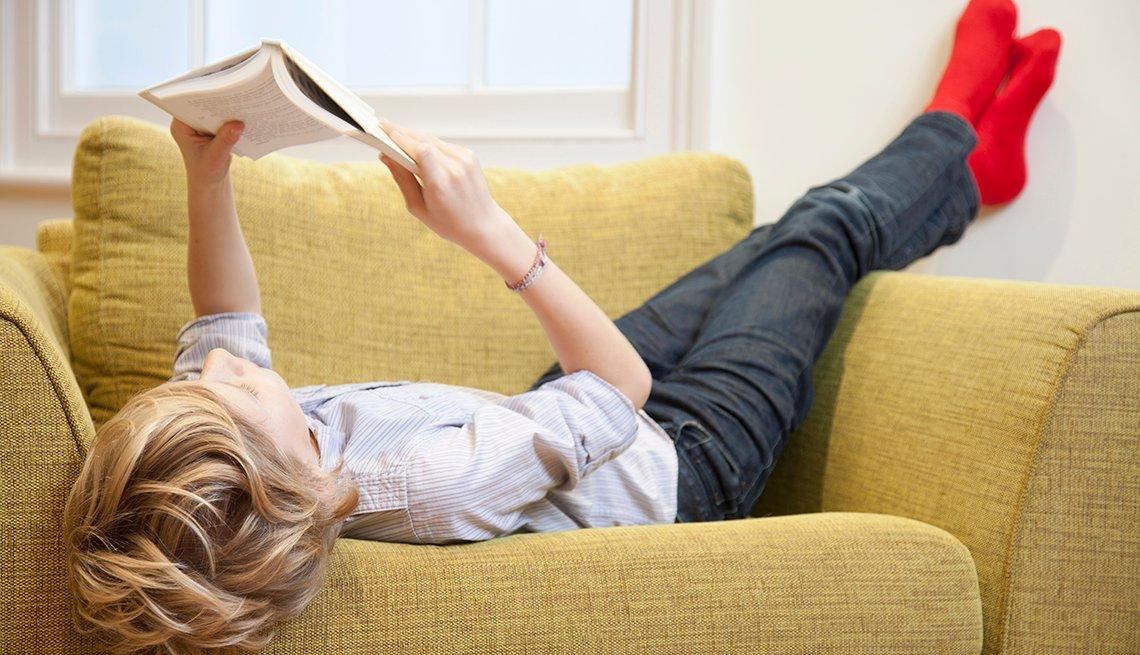 Preadolescente acostado bocarriba en una silla mientras lee un libro.