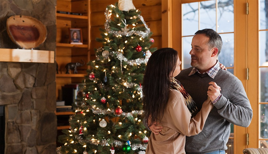 couple slow dancing near a Christmas tree
