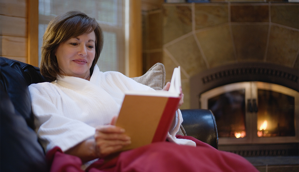 woman sitting on a couch, reading a book by the fire