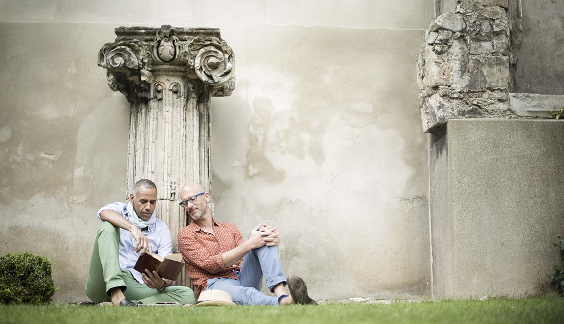 two men read a book in a park