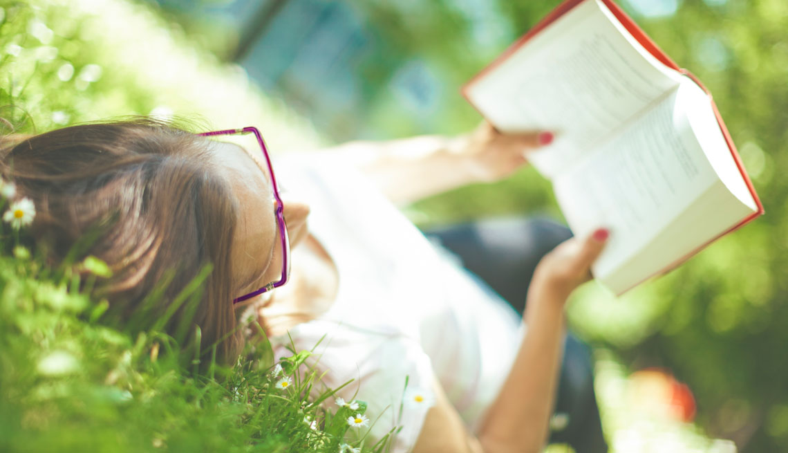 woman reads book on the grass