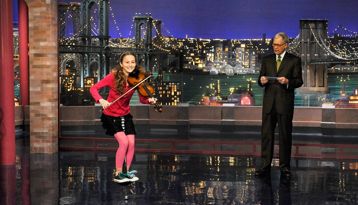 Dea Devlin jumps on a pogo stick and plays violin during Stupid Human Tricks on the Late Show with David Letterman