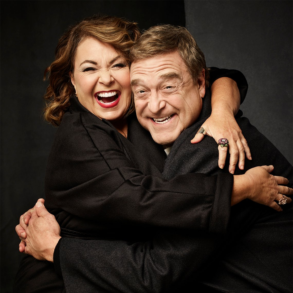 Roseanne Barr and John Goodman laughing and hugging each other