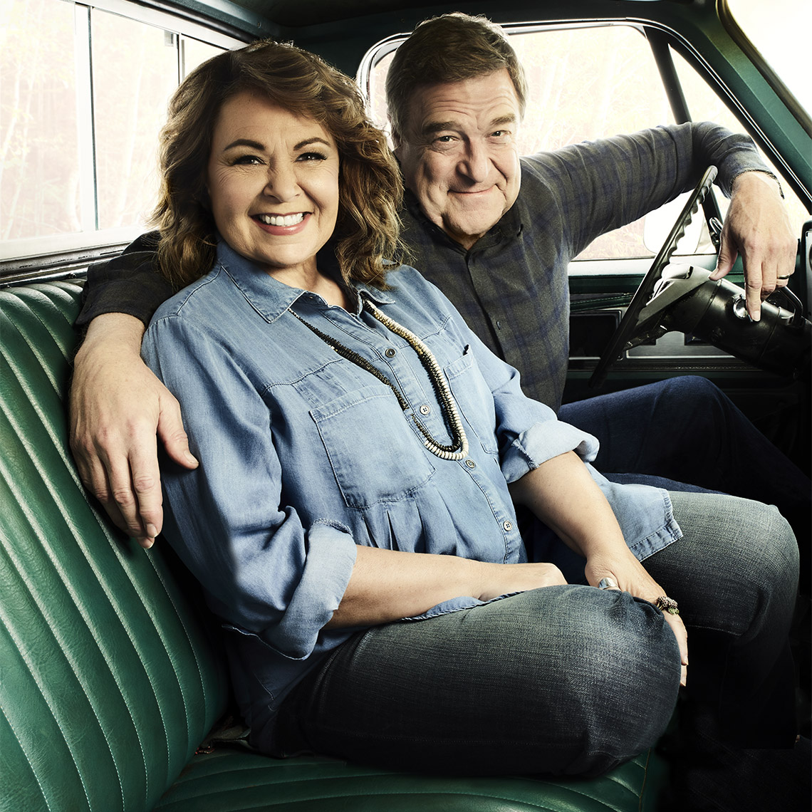Roseanne Barr and John Goodman in the front seat of a old green pickup truck