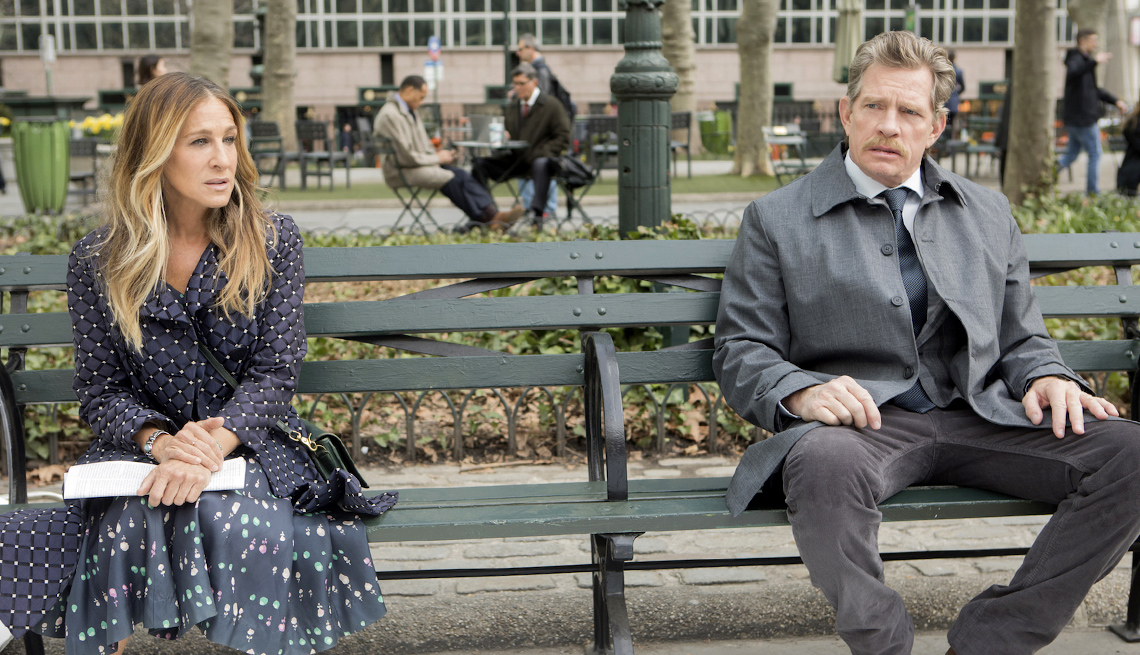 Actors Sarah Jessica Parker and Thomas Hayden Church sitting on a park bench together