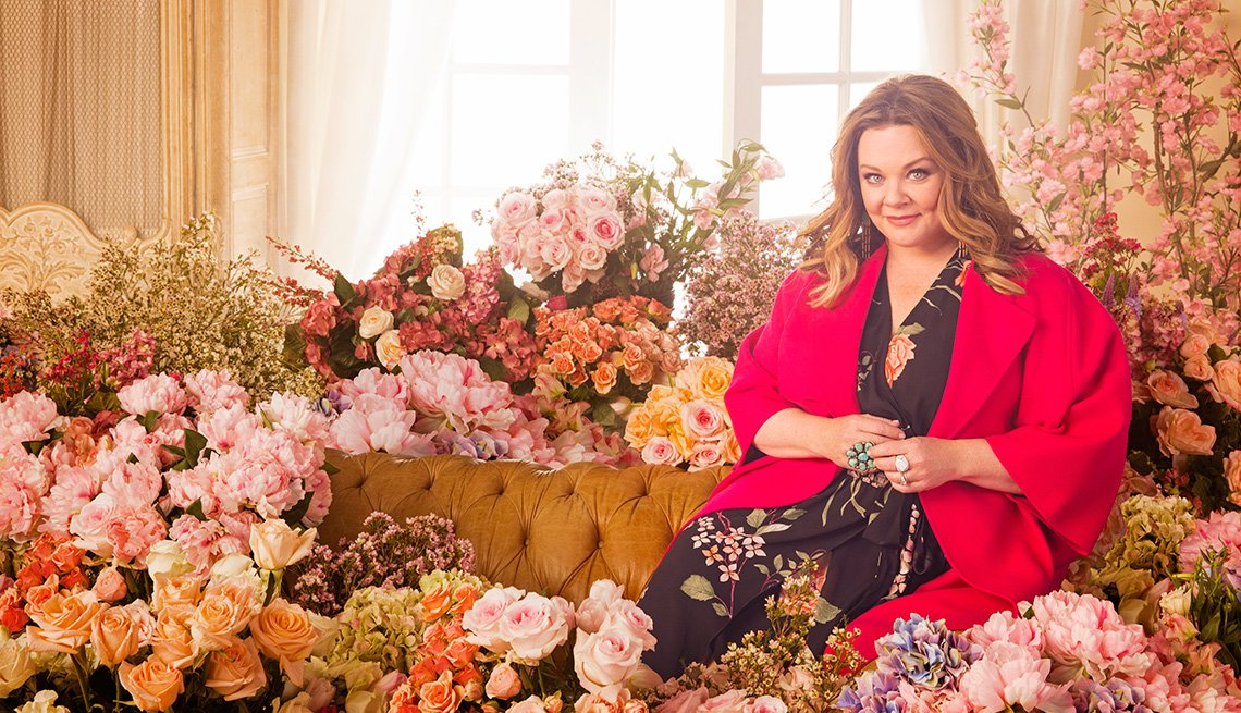 Melissa McCarthy sitting on a couch surrounded by flowers