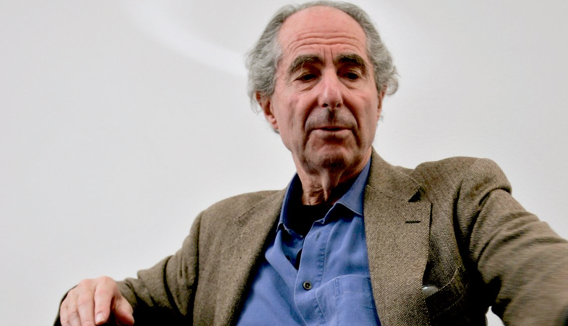 Philip Roth leans back in a chair at a table wearing a suit coat.
