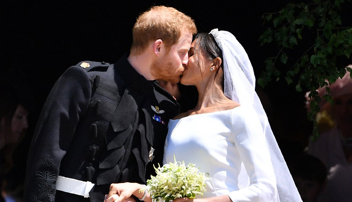 item 2 of Gallery image - Prince Harry, Duke of Sussex kisses his wife Meghan, Duchess of Sussex as they hold hands.