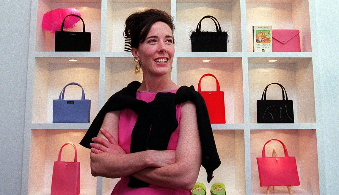 item 15 of Gallery image - Kate Spade standing in front of colorful handbags.