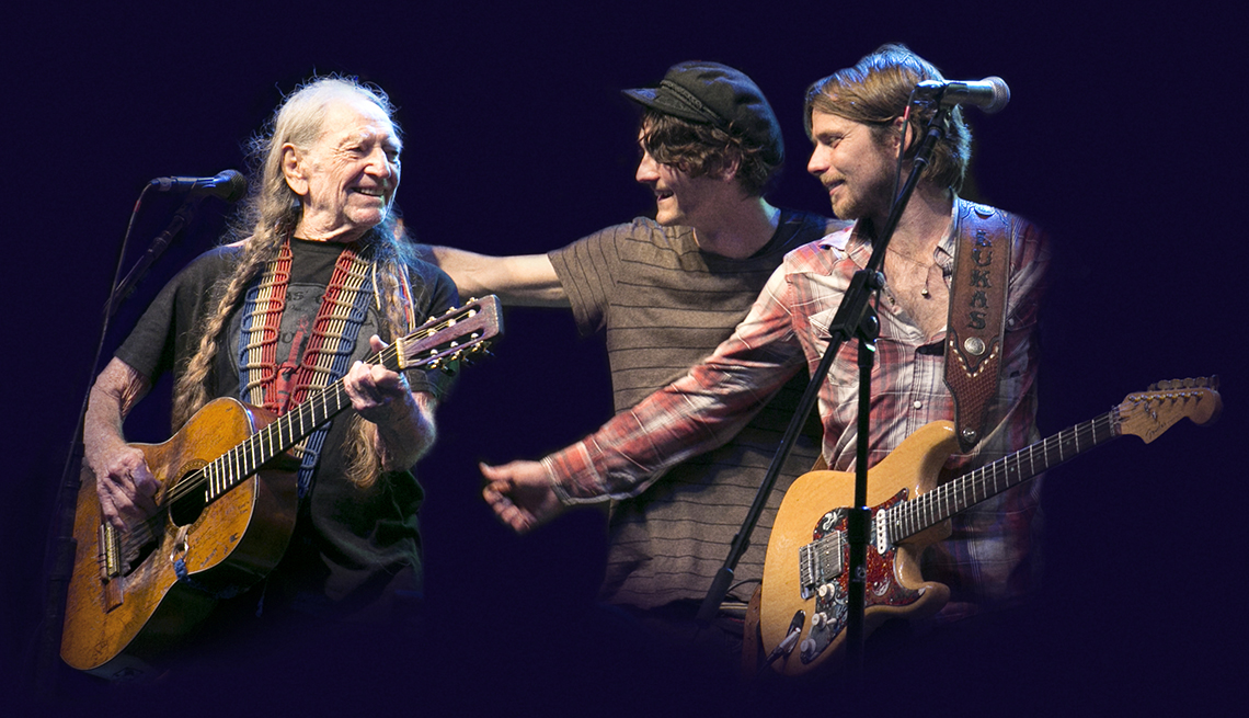Willie Nelson on stage performing with two of his children.