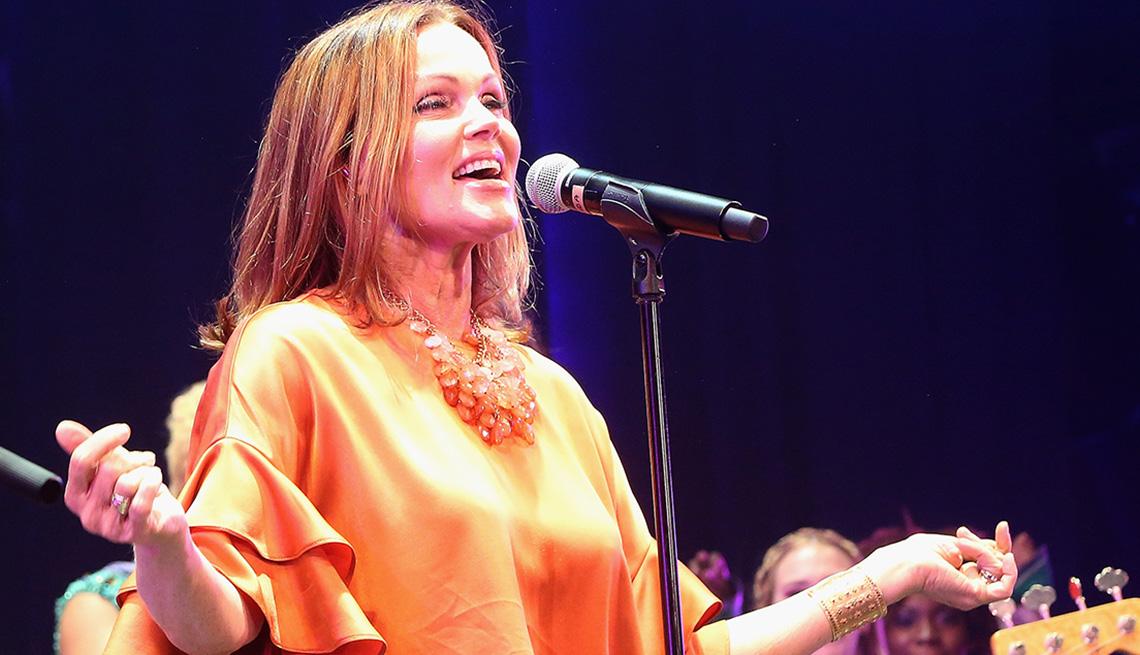 item 5 of Gallery image - Belinda Carlisle standing at a microphone singing.
