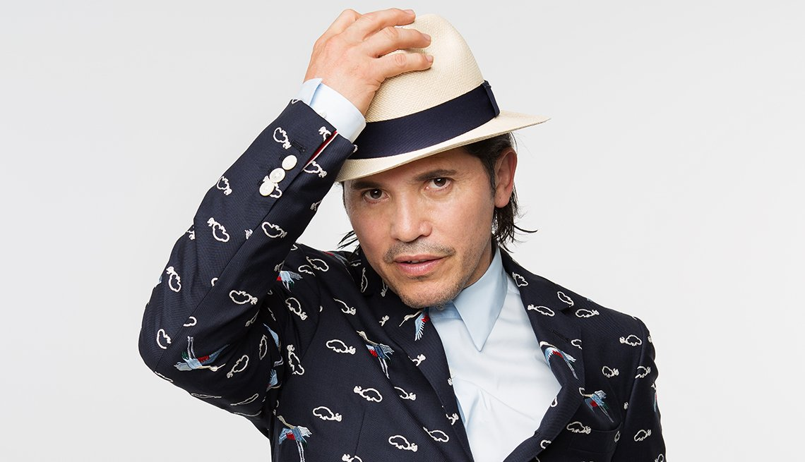 John Leguizamo with his hand on his head.