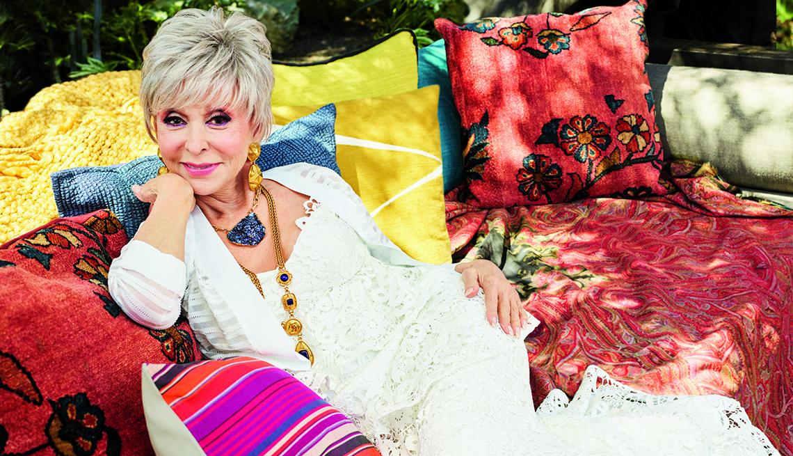Rita Moreno sentada en un sofá al aire libre