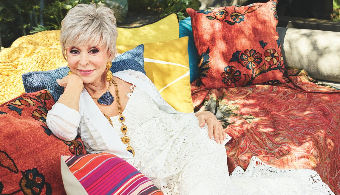 Rita Moreno sitting on a couch outside.