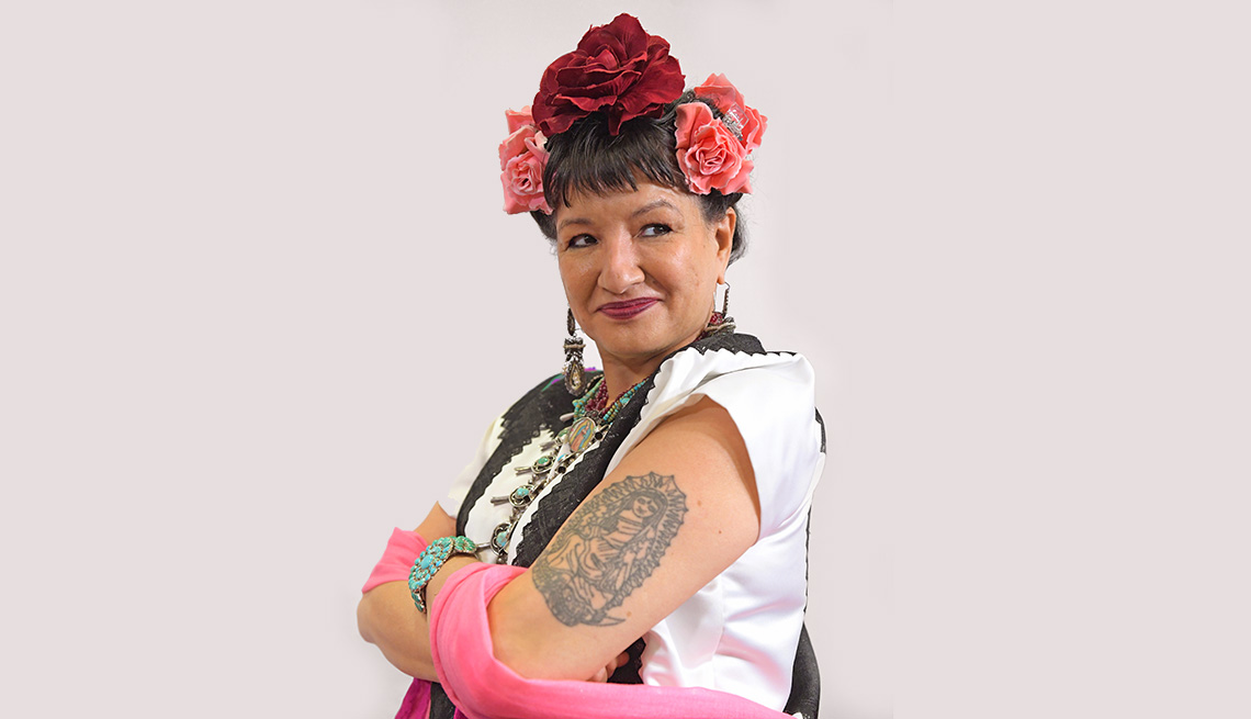 Sandra Cisneros, with flowers in her hair and a tattoo on her arm, looking to the side.