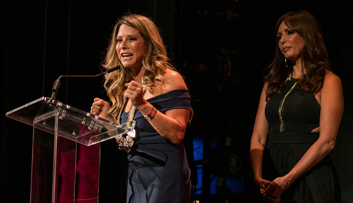 Ingrid Hoffmann stands at the podium accepting her Hispanic Heritage Award. Presenter Giselle Blondet stands beside her.