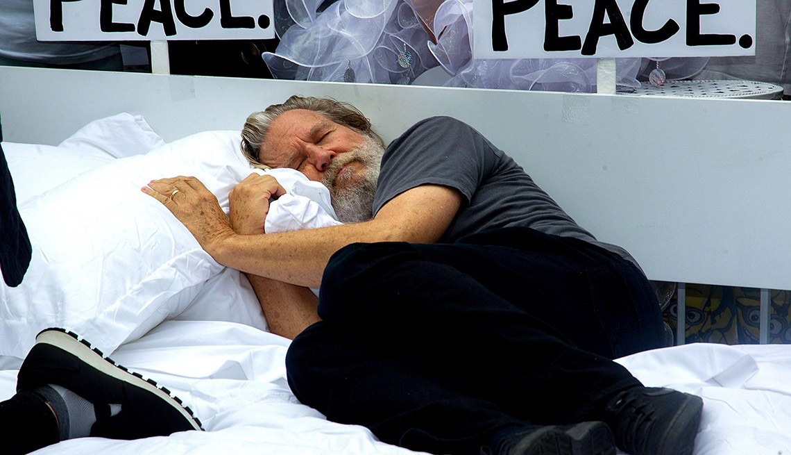 Jeff Bridges laying on a bed for a charity event in NYC