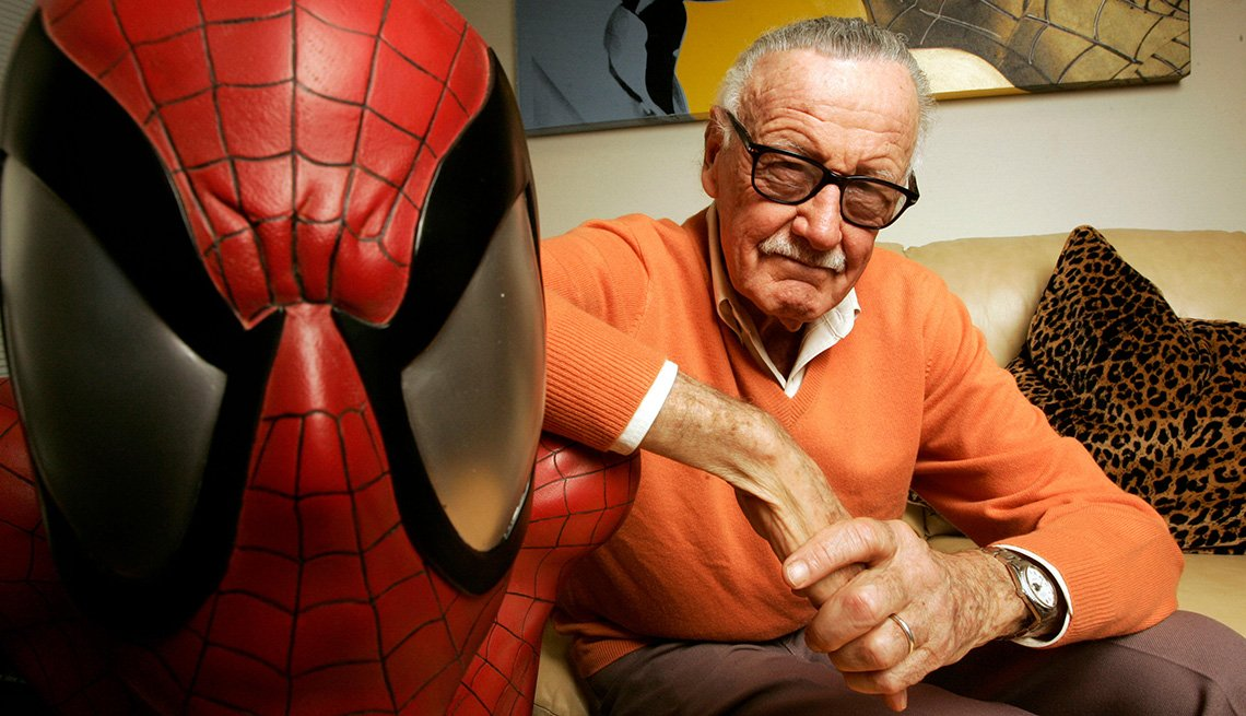 Stan Lee posing for a photo next to Spiderman