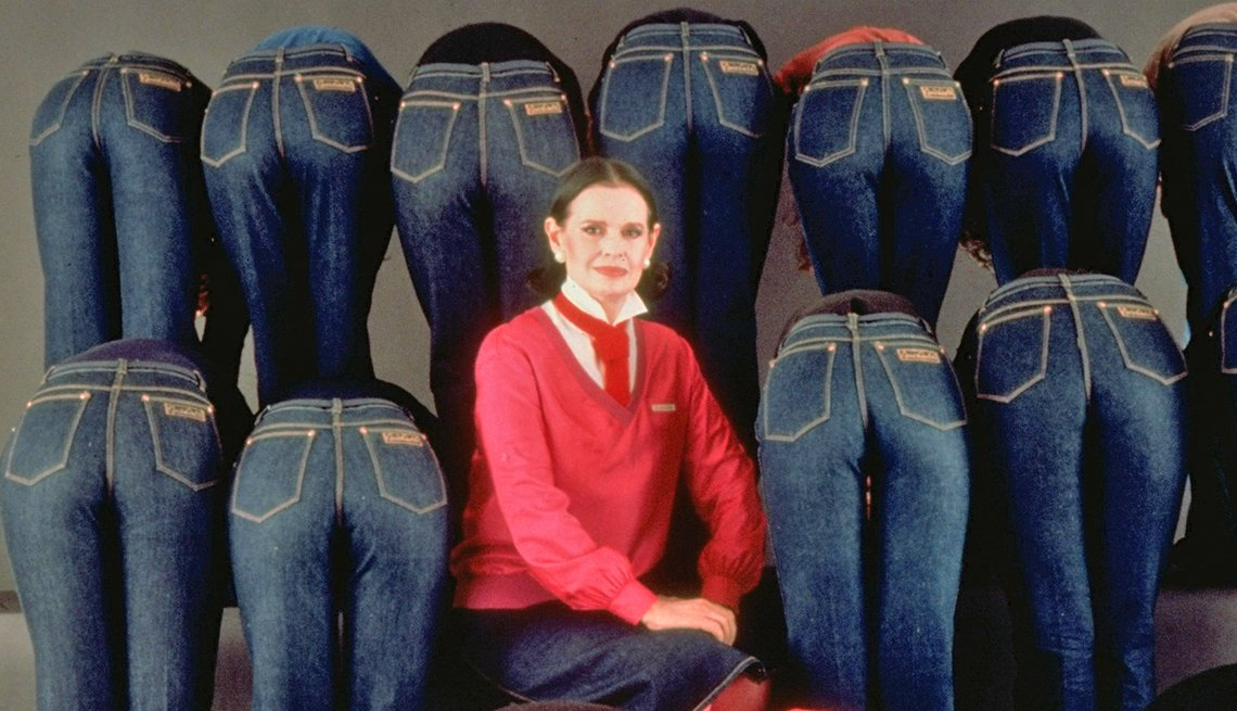 Portrait of socialite/designer Gloria Vanderbilt sitting amidst a group of models bending over to accent the rear of her designer jeans.