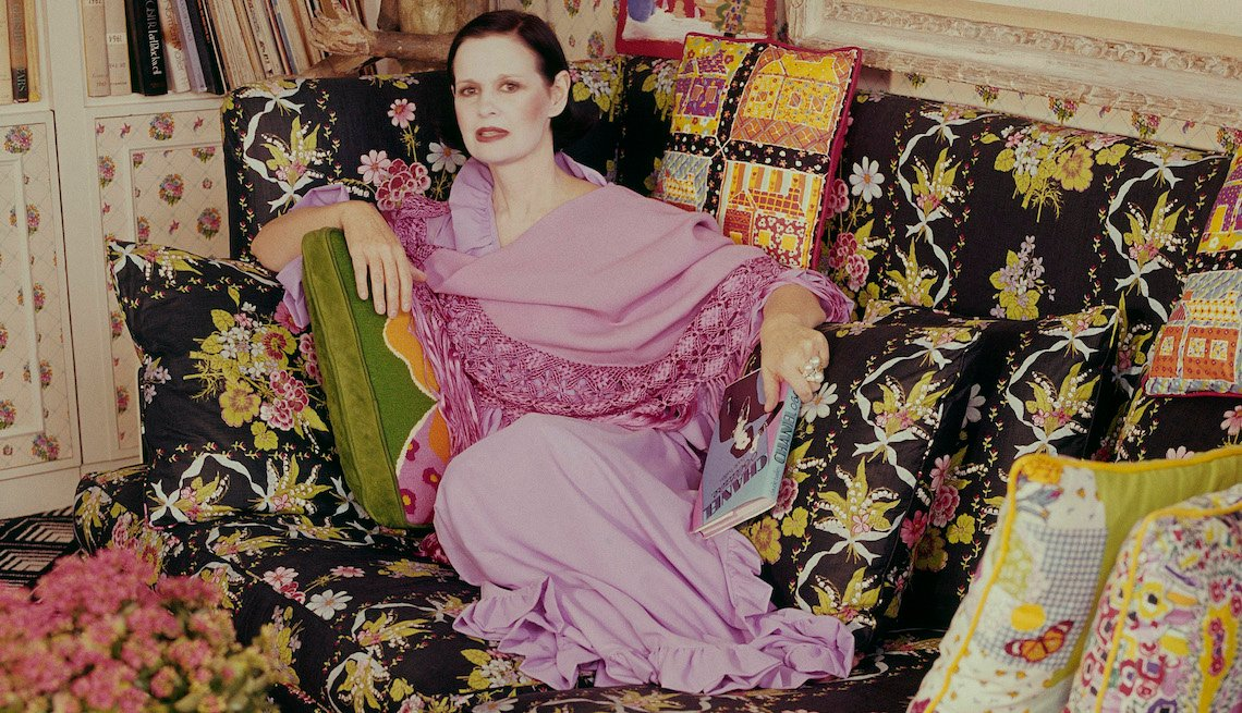 Gloria Vanderbilt culred up on a couch with flowered printed pillows she designed.