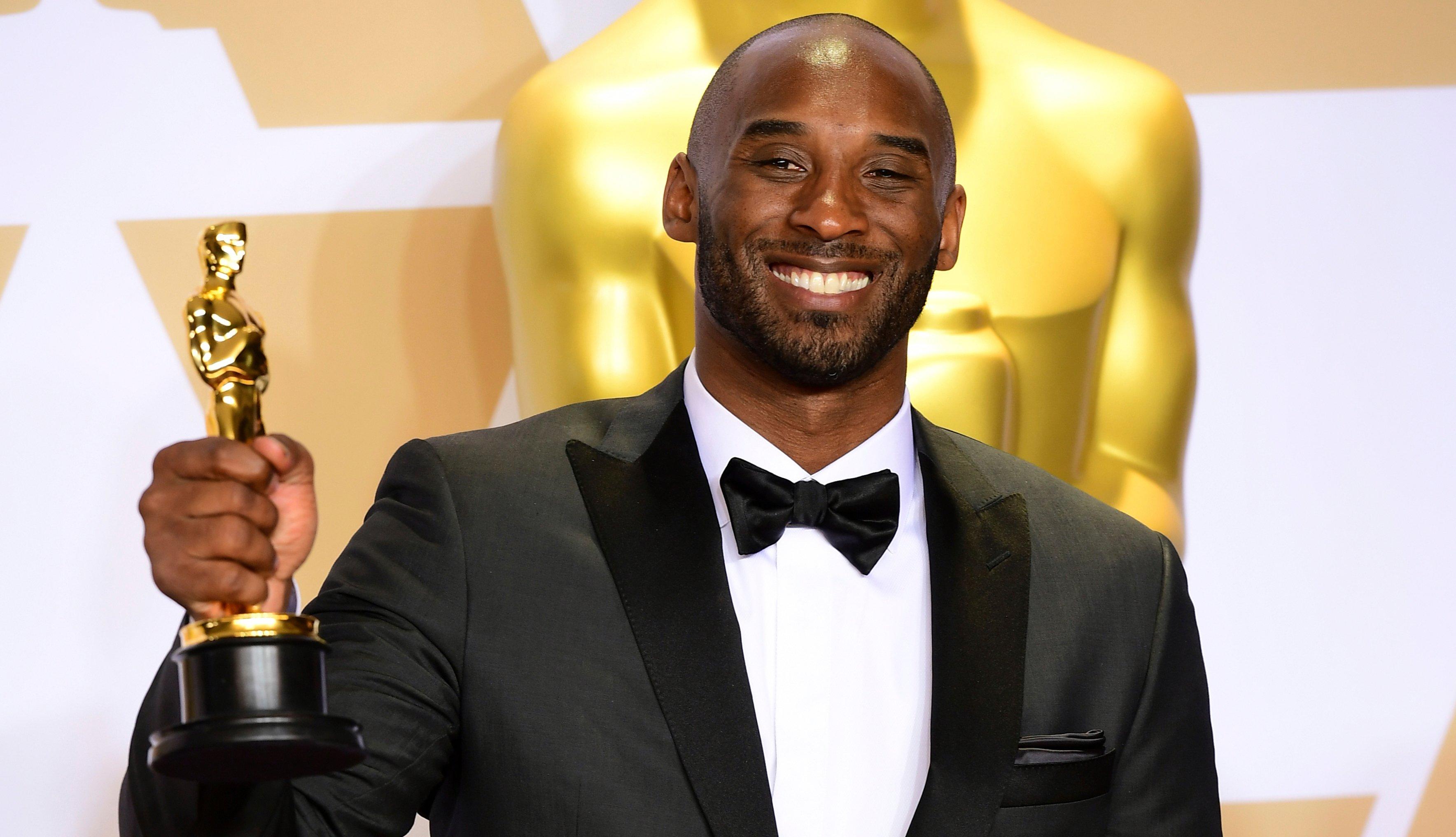 Kobe Bryant sonríe mientras sostiene su estatuilla del Óscar, 2018.