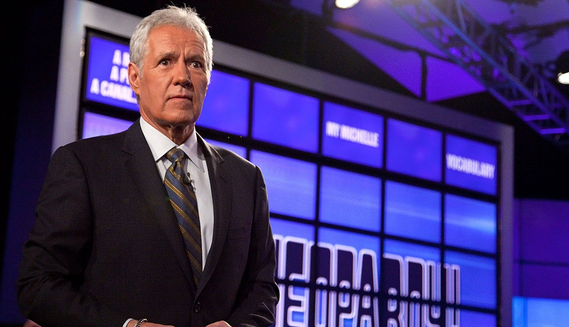 Jeopardy host Alex Trebek standing in front of a board of monitors used for the game show