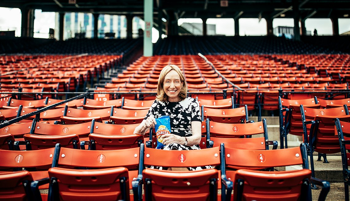doris kearns goodwin sits in the stands of an empty baseball stadium holding a bag of peanuts