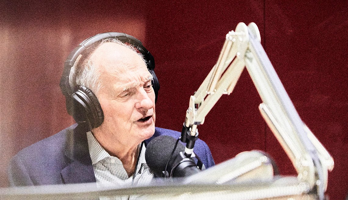 actor alan alda hosting a podcast talking into a microphone in a sound booth