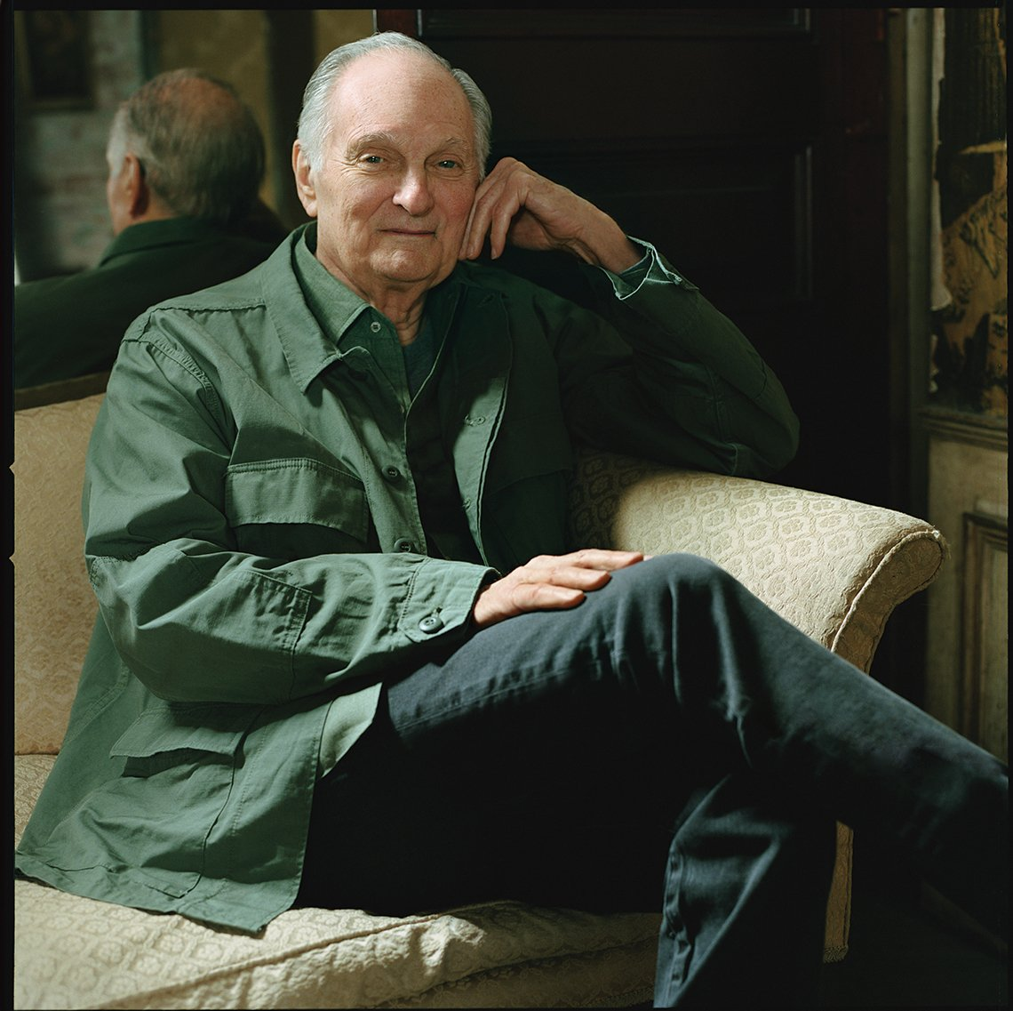 actor alan alda sits cross legged on a couch