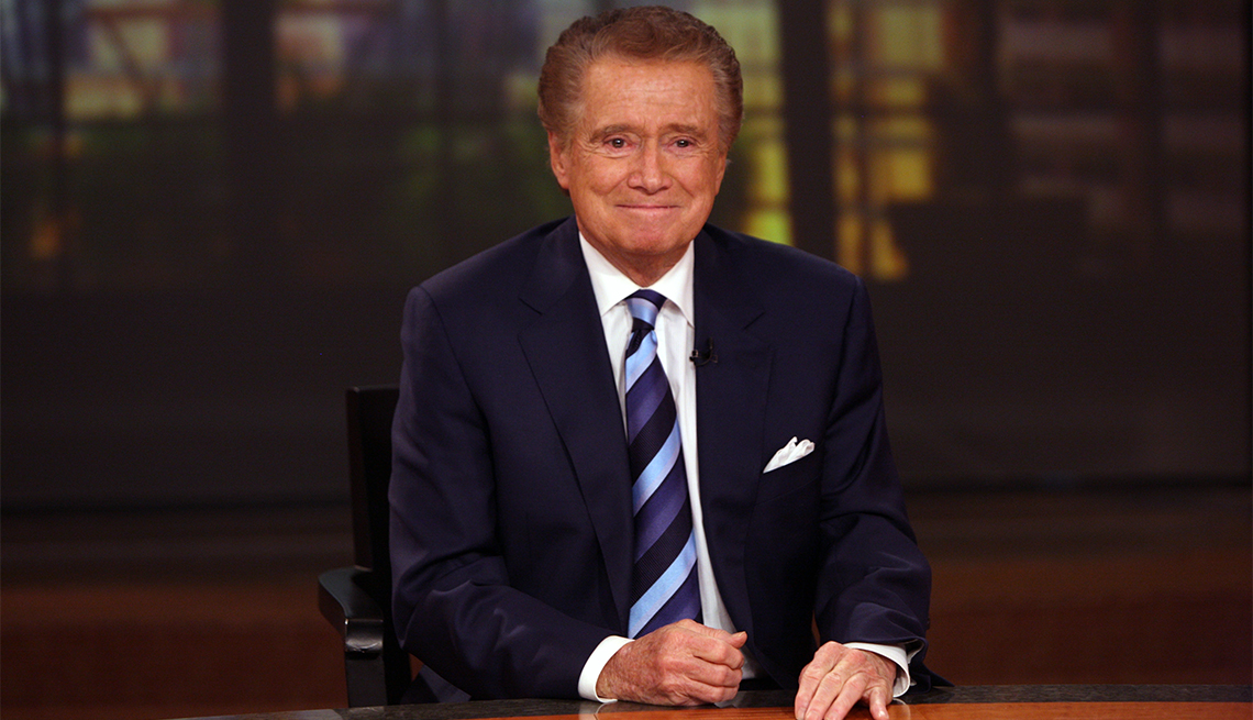 item 30 of Gallery image - Regis Philbin sitting behind a television studio desk