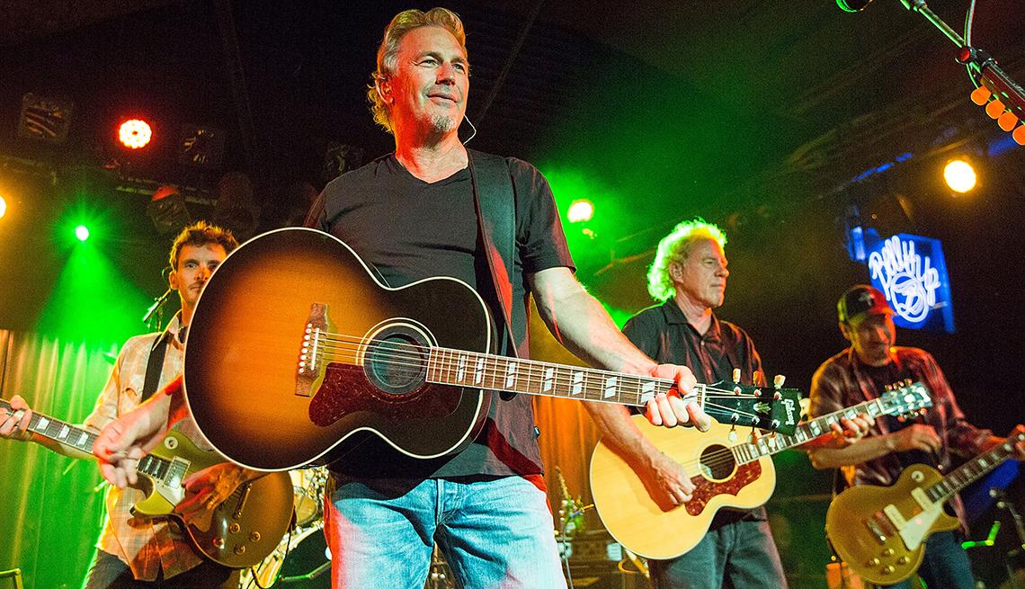 Kevin Costner con una guitarra en un escenario con su banda  de country-rock, Modern West, Solana Beach, California.
