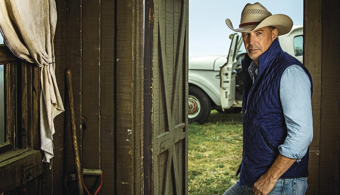 Kevin Costner en una casa de campo con sombrero, chaleco y una camioneta antigua al fondo.