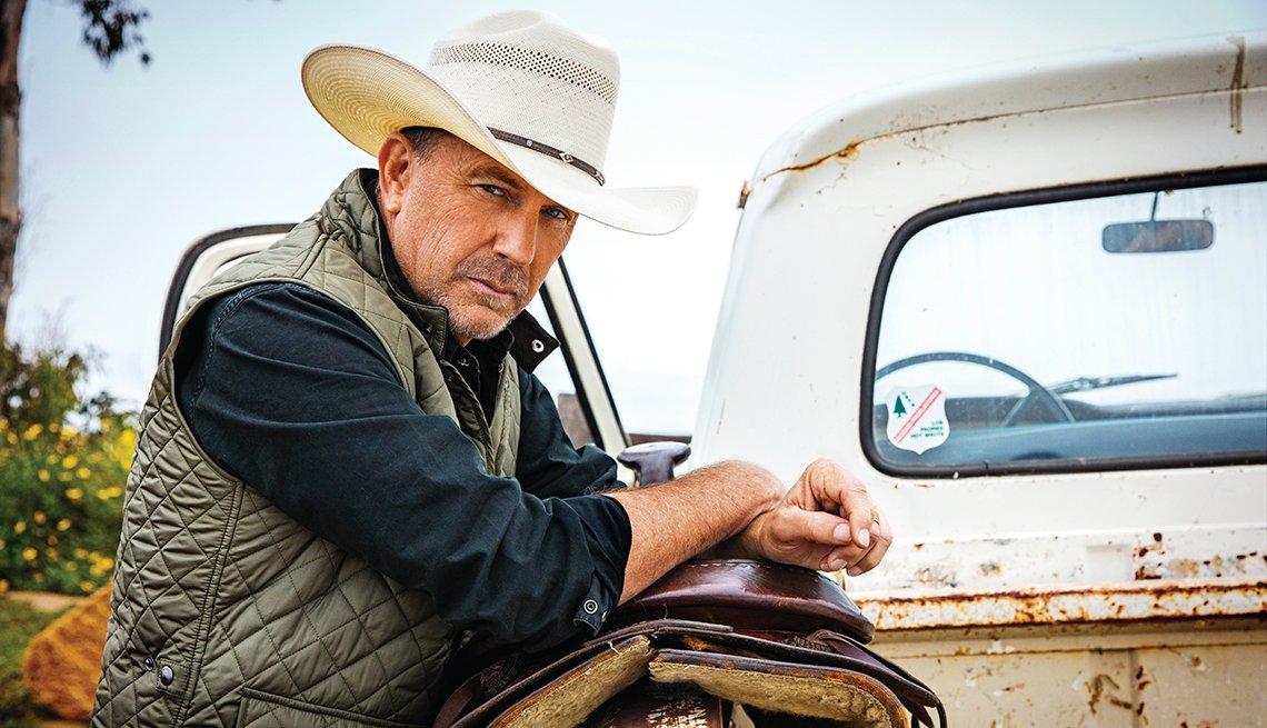 Retrato de Kevin Costner recostado sobre una silla de caballo en la parte trasera de una camioneta antigua.