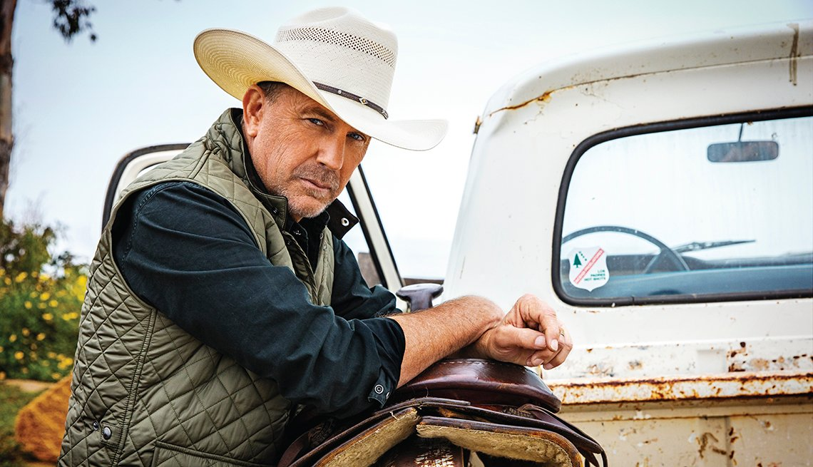portrait of kevin costner leaning against a horse saddle in the back of an old farm pickup truck
