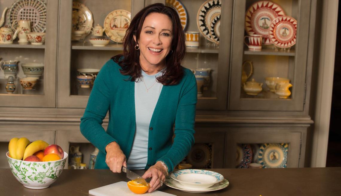 patricia heaton in a kitchen slicing an orange